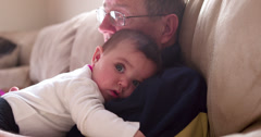 Calm baby laying on Grandpa 4k Stock Footage