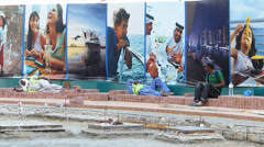 Dubai cheap foreign migrant construction workers rest under promotion billboard Stock Footage