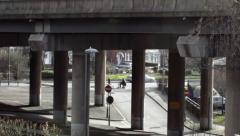 Street scene seen through the pillars of the bridge highway Stock Footage