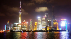 Brightly lit ship passing Shanghai huangpu river at night,Lujiazui business hub Stock Footage
