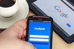 Entrance to the social network facebook via mobile phone htc. Stock Photos