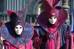 Two persons in costume at st. mark's square during the carnival of venice,italy Stock Photos