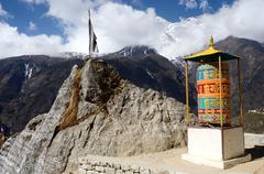 buddhist mani stones prayer wheels with sacred mantras near namche bazaar,cap - stock photo