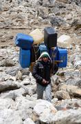 Sherpa porter carry heavy load in the himalaya at everest base camp trek Stock Photos