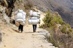 Two sherpa porters carrying heavy sacks in himalaya at everest base camp,nepal Stock Photos