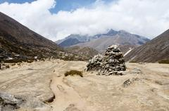 Buddhists prayer flags and stone pyramids often marks the mountain pass Stock Photos