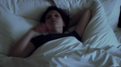 Woman has insomnia, tosses and turns in bed - wide shot Stock Footage
