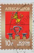 russia - circa 2013: a stamp printed in russia shows coat of arms of the town - stock photo