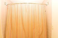 Bath tub behind striped colourful curtain - stock photo