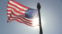 The American flag is waving with a bright sun behind - stock footage