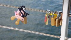 Pacifiers and padlocks hanging on a bridge Stock Footage