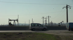 Shut down oil pumpjack, donkey pumpers near main road, oil well pumps, crude oil Stock Footage