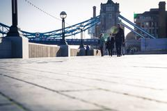 people commute at southbank near tower bridge - stock photo