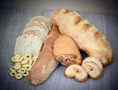 Stock Photo of Fresh Tasty Bread on Woody Background