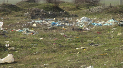 Pollution at a landfill with waste and trash on a field Stock Footage