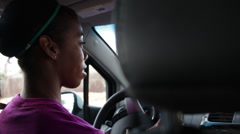 Black girl driving the car, talks to the girl seating nearby - stock footage