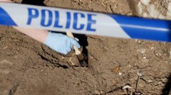 Uncovering skull at crime scene Stock Footage