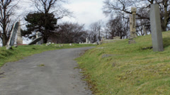 Static shot of old churchyard - path, graves and church tower Stock Footage