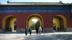 Asian People walk in cypress trees park,China Beijing red door ancient building Stock Footage
