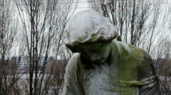 Moldy, stone statue of a woman with head bent down in prayer position Stock Footage