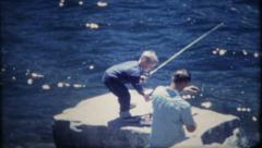 121 - father and son fishing together at the lake - vintage film home movie Stock Footage