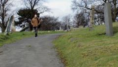 Guy in winter coat walks graveyard path towards the camera Stock Footage