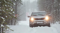 Stuck in the snow car is headlights turned on are on the forest winter road - stock footage