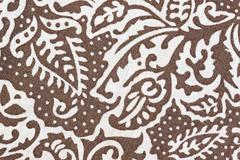 white patterned leaves on brown fabric. - stock photo