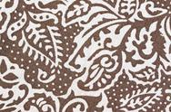 Stock Photo of white patterned leaves on brown fabric.