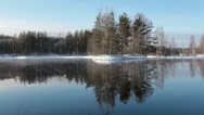 Stock Video Footage of Calm forest lake in winter, Karelia. Steam from the water surface. Camera review
