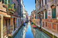 Stock Photo of narrow canal among ancient houses. venice, italy.