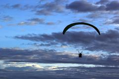 Silhouette of paragliding on beautiful sky background Stock Photos