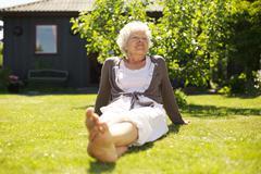 senior woman enjoying the fresh air in garden - stock photo
