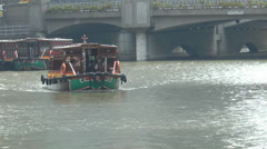 A bumboat cruising on Singapore River near Coleman Bridge. (SG RIVER--109a) - stock footage