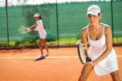 Women playing doubles at tennis Stock Photos