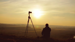 The photographer sits near tripod by picturesque sunset - stock footage