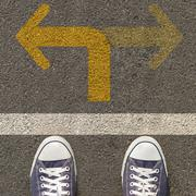 pair of shoes standing on a road with two way yellow arrow - stock photo