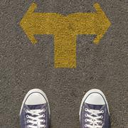 Pair of shoes standing on a road with two way yellow arrow Stock Photos
