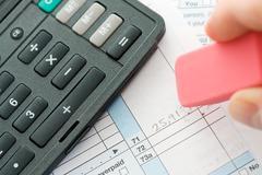 taxes: erasing incorrect figures on tax form - stock photo