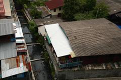 slum near dirty canal in bangkok, thailand - stock photo