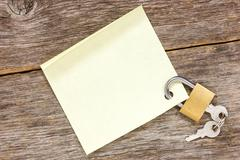 Stock Photo of padlock with empty  sticky note