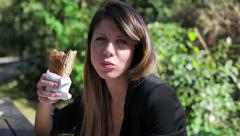 Beautiful young excited woman eating a hot dog in a park Stock Footage