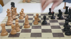Hands of a two chess players and black pawn take white pawn Stock Footage