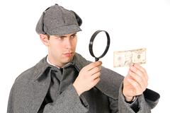 sherlock: curious detective looks at money with magnifying glass - stock photo
