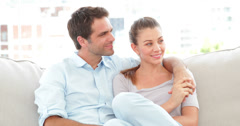 Couple relaxing on the couch and smiling at camera Stock Footage