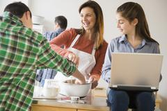 Caucasian family baking and using laptop in kitchen Stock Photos
