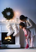 Black mother and daughter looking at Christmas stockings Stock Photos