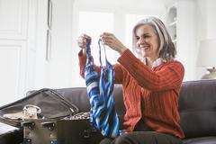 Valkoihoinen nainen pakkaus uimapukua matkalaukku Kuvituskuvat