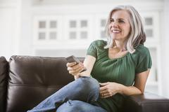 Happy Caucasian woman watching TV on sofa Stock Photos