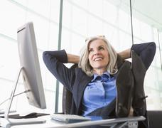 Confident Caucasian businesswoman with feet up on desk Stock Photos